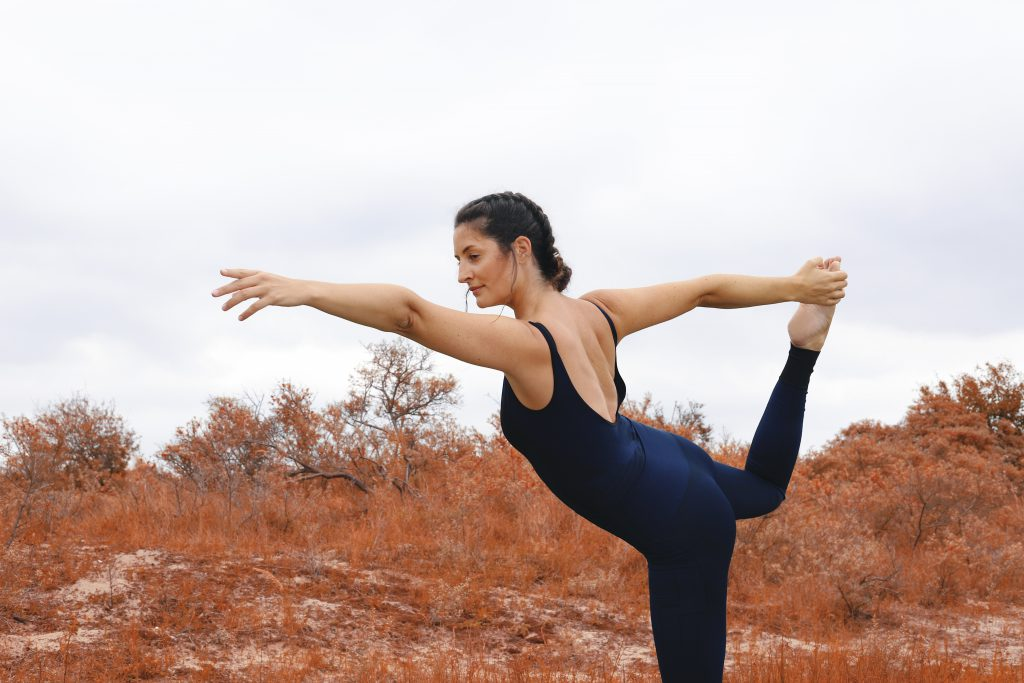 Girl doing yoga dancesr pose in activewear singlet outdoor