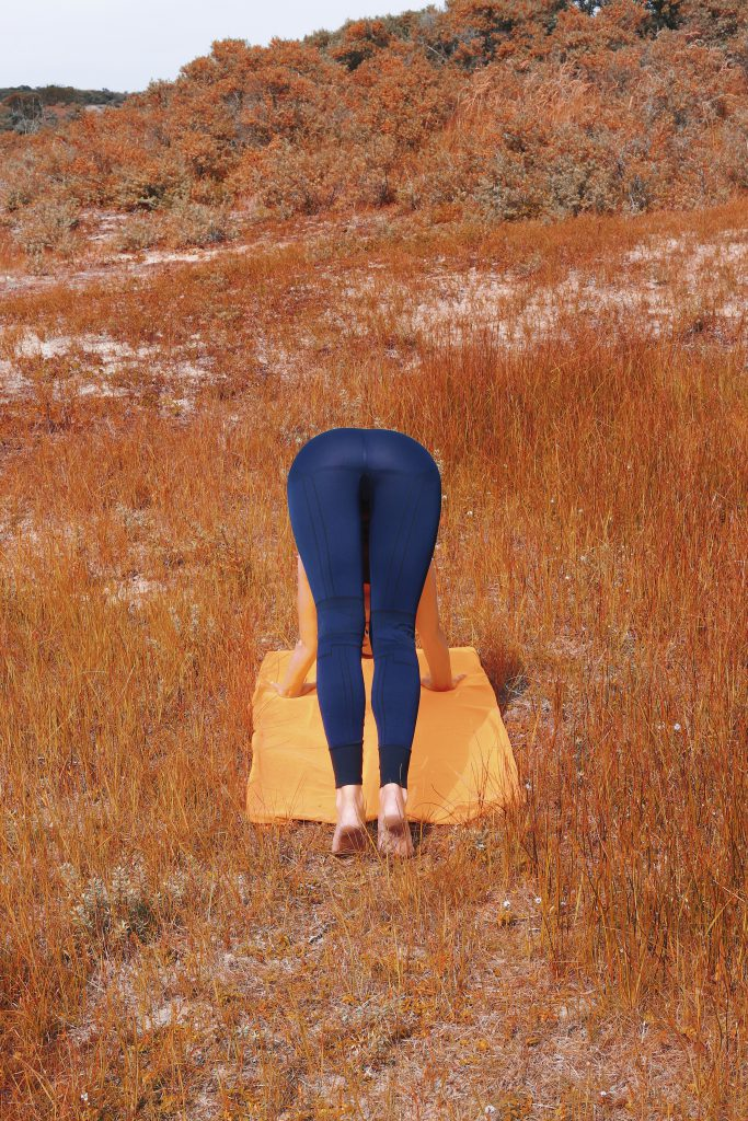 girl doing downward facing dog in blue activewear legging