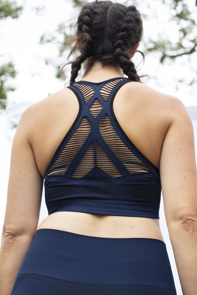 backside girl wearing activewear bra top with ladder knit structure